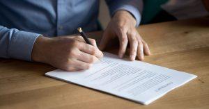 man som skriver kontrakt av försäljning av ett företag